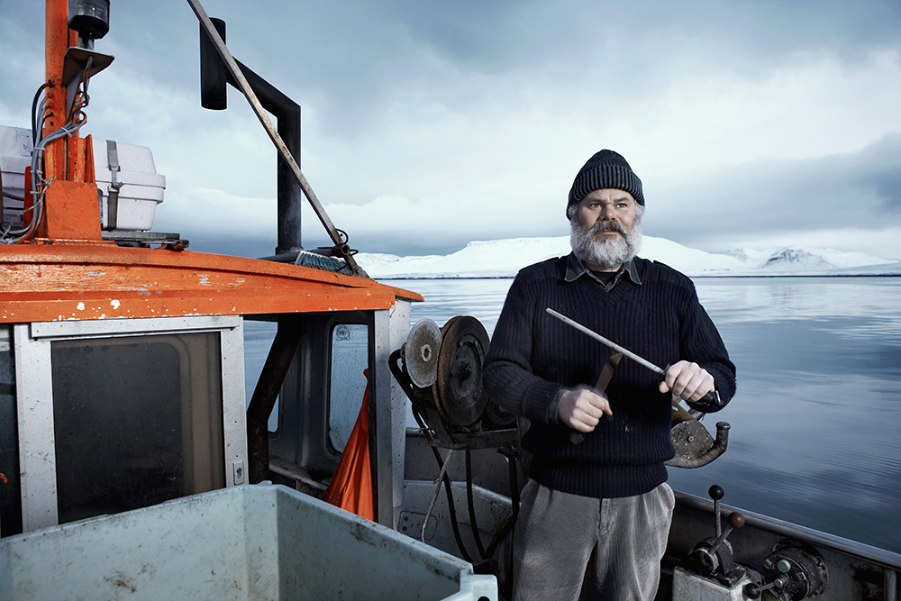 600-06732727 © Atli Mar Hafsteinsson Model Release: Yes Property Release: Yes  Fisherman with gray beard, standing on small boat sharpening a knife on a winter day, Iceland.