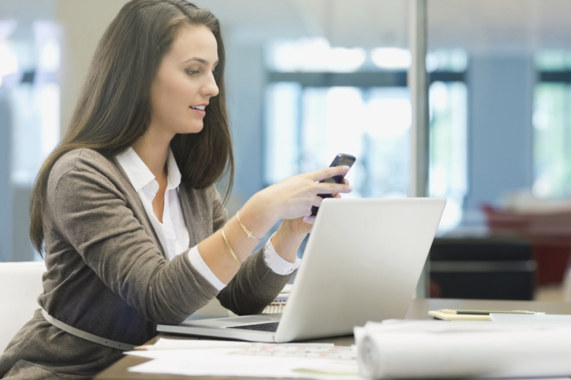 a-government-woman-employee-uses-a-smartphone-and-laptop-in-the-office