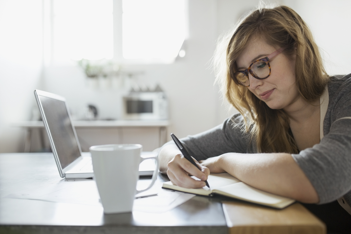 stock-photo-businesswoman-writing-in-notebook-at-laptop-84994995
