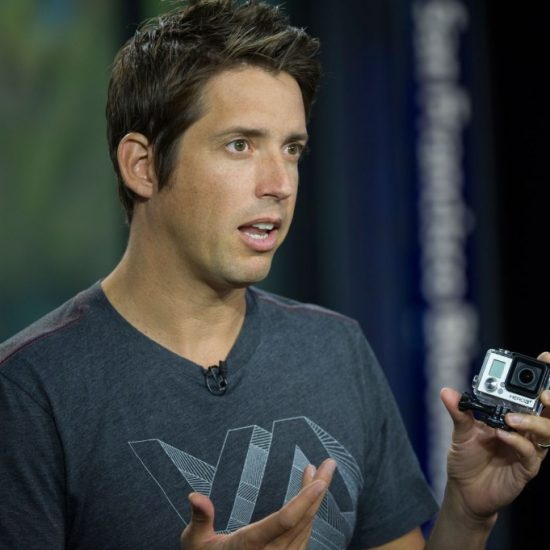 """Nicholas """"Nick"""" Woodman, founder and chief executive officer of GoPro, holds a GoPro Hero 3+ camera as he speaks during a Bloomberg West television interview in San Francisco, California, U.S., on Monday, Sept. 30, 2013. GoPro, maker of extreme sports cameras, launched the new GoPro Hero 3+ camera on Oct. 1. Photographer: David Paul Morris/Bloomberg via Getty Images"""